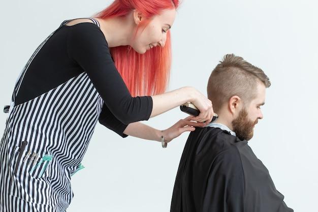 Koncepcja salonu fryzjerskiego, stylistka i fryzjera - fryzjerka kobieta tnie mężczyznę.