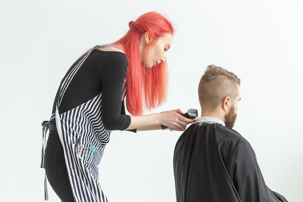 Koncepcja salonu fryzjerskiego, stylistka i fryzjera - młoda fryzjerka będzie ścinać mężczyźnie włosy