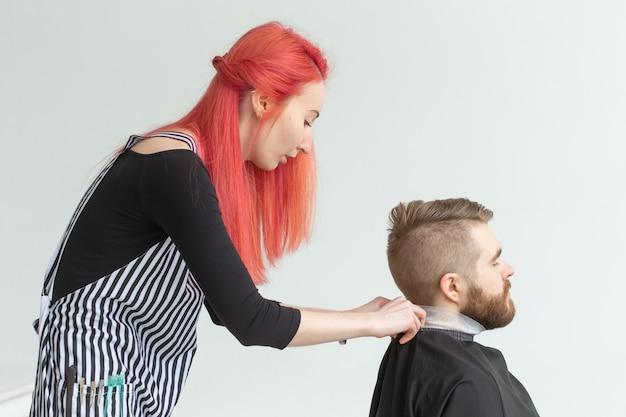 Koncepcja salonu fryzjerskiego, stylistka i fryzjera - młoda kobieta fryzjerka będzie ścinać mężczyznę