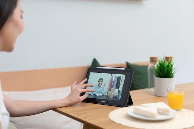 Koncepcja salonu kobieta za pomocą swojego urządzenia elektronicznego do pracy zdalnej w przytulnym pokoju kawiarni.
