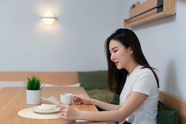 Koncepcja salonu ładna pani czytająca artykuł na papierze, podczas gdy druga ręka trzyma kubek napoju z kofeiną rano.