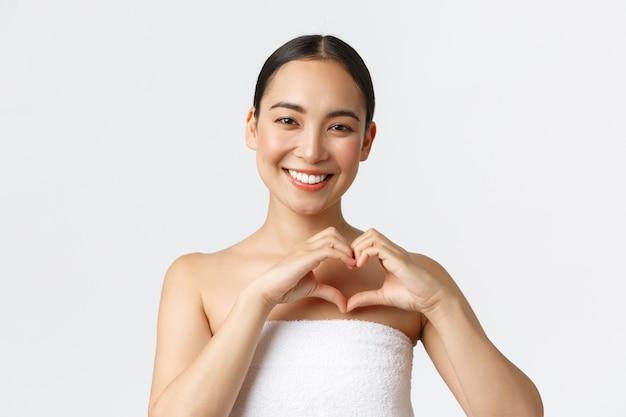 Koncepcja salonu piękna, kosmetologii i spa. charyzmatyczna uśmiechnięta azjatka w ręczniku pokazująca gest serca zadowolona, polecam klinikę urody, zadowolona po masażu, biała ściana.