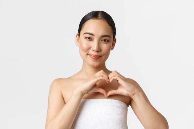Koncepcja salonu piękna, kosmetologii i spa. kobieca piękna azjatka w ręczniku uśmiechnięta zadowolona i pokazująca gest serca, zakochana w personelu kliniki kosmetycznej i produktach do pielęgnacji skóry, biała ściana.