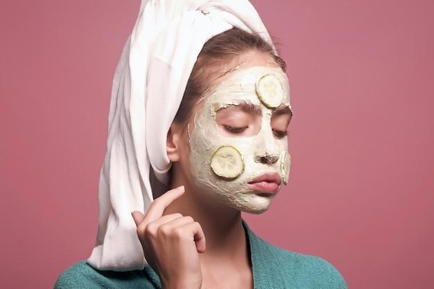 Koncepcja salonu piękności. pielęgnacja skóry młodej kobiety. twarz kobiety z maską ogórkową. dziewczyna rano