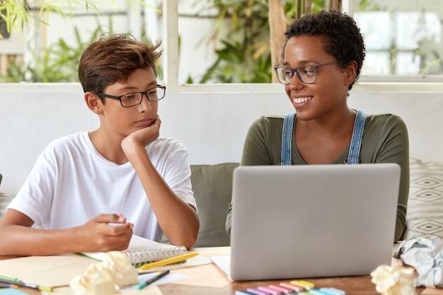 Koncepcja samokształcenia i e-learningu. zadowolona czarna wolontariuszka próbuje wyjaśnić młodemu uczniowi swoją strategię