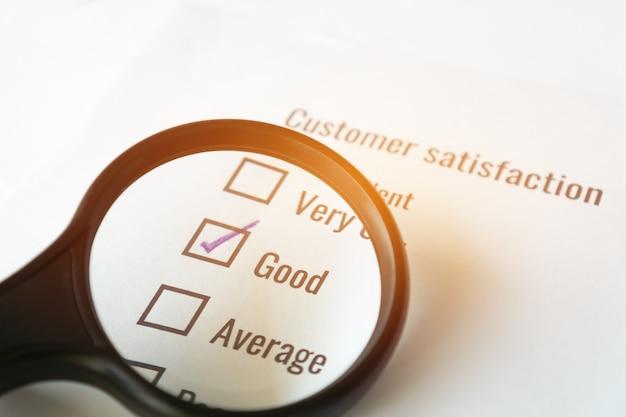 Koncepcja satysfakcji opinii z ankiety: klient używa szkła powiększającego do listy kontrolnej dobrej nad dokumentem formularza wniosku. wypełnianie pytania o opinię znacznik wyboru dla badań marketingowych w biznesie