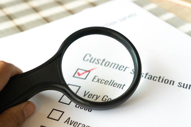 Koncepcja satysfakcji opinii z ankiety: klient używa szkła powiększającego do listy kontrolnej doskonałej nad dokumentem formularza wniosku. wybór pytania do opinii wypełnij znacznik wyboru dla badań marketingowych w biznesie