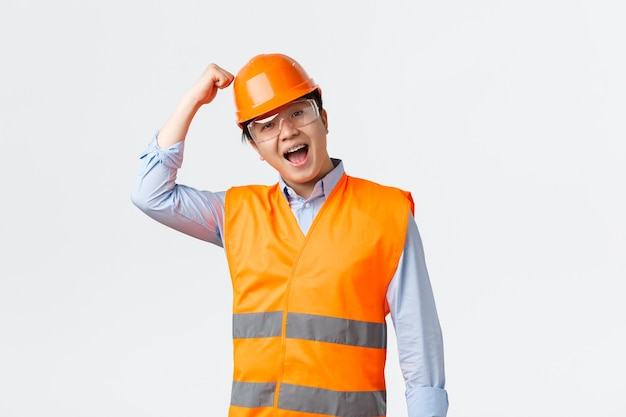 Koncepcja sektora budowlanego i pracowników przemysłowych. entuzjastyczny męski inżynier w odblaskowej odzieży, pukający w kask i uśmiechający się, zapewnia pracownikom pracującym z dobrą ochroną, białe tło.