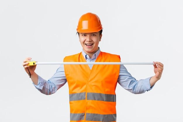 Koncepcja sektora budowlanego i pracowników przemysłowych pewny siebie entuzjastyczny azjatycki inżynier budowlany za sterami ...