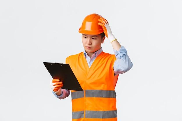 Koncepcja sektora budowlanego i pracowników przemysłowych poważnie wyglądający zdziwiony inżynier azjatycki inspektor w fa...