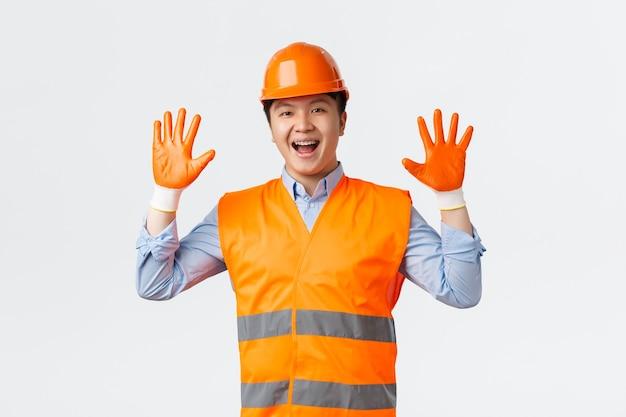Koncepcja sektora budowlanego i pracowników przemysłowych wesoły uśmiechnięty azjatycki budowniczy kierownik budowy a...