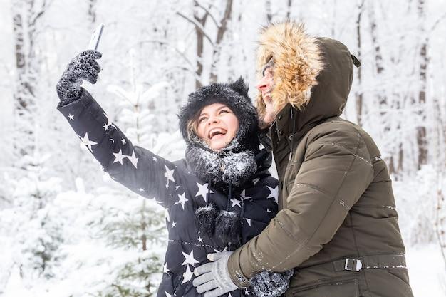 Koncepcja sezonu i relacji - zabawna para przy selfie w okresie zimowym