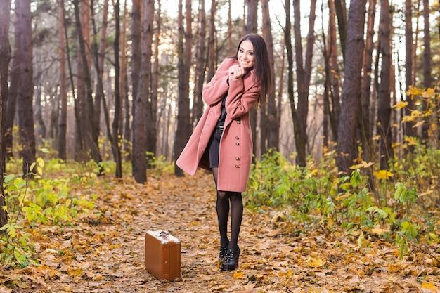 Koncepcja sezonu, przyrody i ludzi - kobieta w parku jesień spaceru z walizką retro