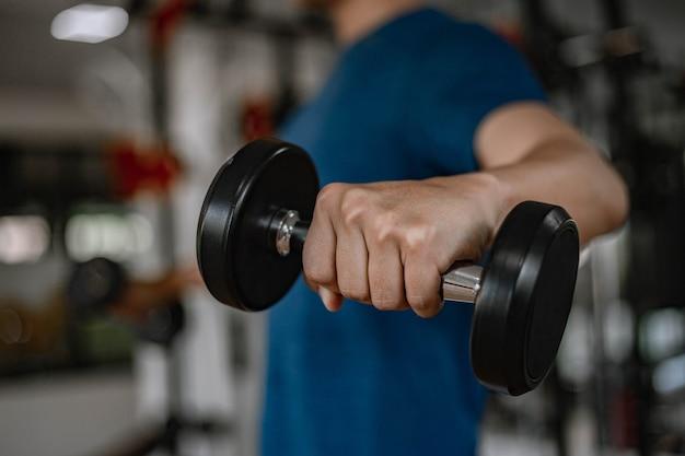 Koncepcja siłowni treningowej młody dorosły za pomocą jego mięśni silne ramię podnosząc hantle w górę iw dół na siłowni.