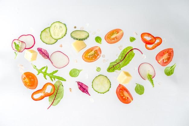 Koncepcja składników sałatki wiosennej. zdrowa żywność na białym tle. warzywa, pomidory, papryka, zielone liście. leżał na płasko, widok z góry, miejsce na kopię