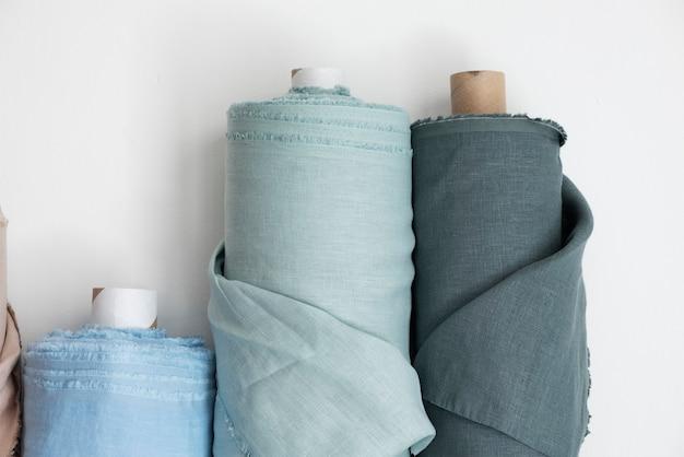 Koncepcja sklepu z draperiami. rolki różnych kolorów bielizny na jasnej ścianie, selektywny obraz ostrości