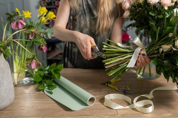 Koncepcja sklepu z kwiatami. kwiaciarnia kobieta tworzy bukiet kwiatów. piękny bukiet kwiatów mieszanych. przystojny świeży pęczek. dostawa kwiatów