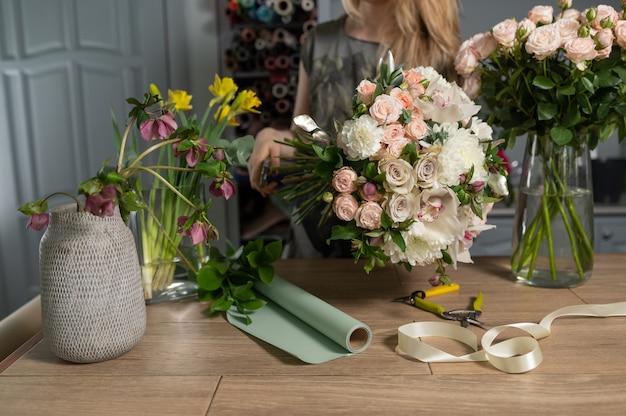 Koncepcja sklepu z kwiatami. kwiaciarnia kobieta tworzy bukiet kwiatów. piękny bukiet kwiatów mieszanych. przystojny świeży pęczek.