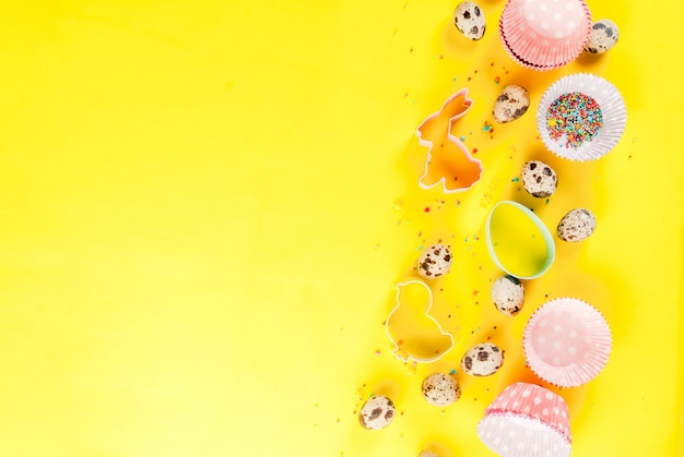 Koncepcja słodkiego pieczenia na wielkanoc, gotowanie z pieczeniem - wałek do ciasta, trzepaczka do ubijania, foremki do ciastek, jajka przepiórcze, posypanie cukrem