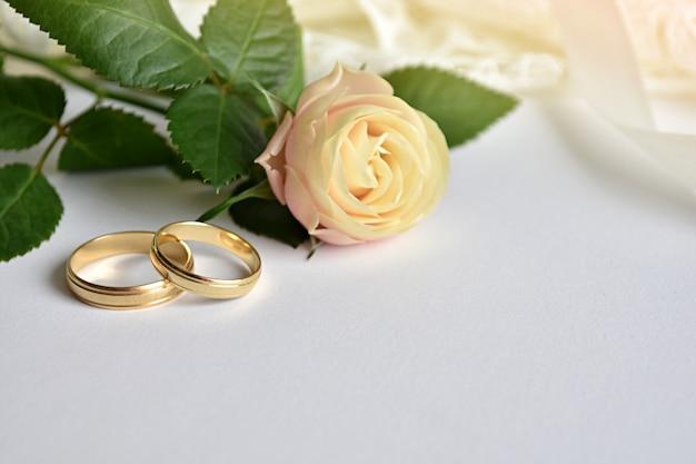 Koncepcja ślubna, dwa złote pierścienie, róża i biała sukienka.