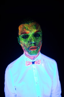 Koncepcja ślubnej sesji zdjęciowej w neonowym oświetleniu w modnym stylu pan młody młody chłopak świeci w ciemności pozuje w białym garniturze ślubnym z muszką pod promieniami uv na ciemnym tle w studio