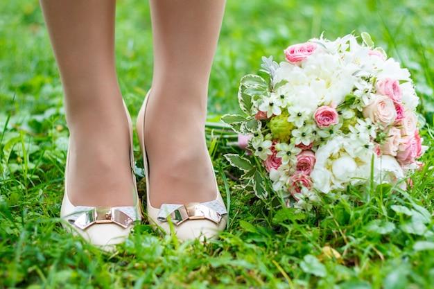 Koncepcja ślubu. bukiet i buty na trawie