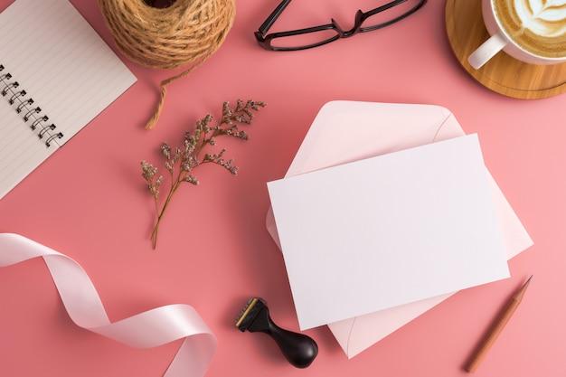 Koncepcja ślubu. ślubna zaproszenie karta na różowym tle z faborkiem i dekoracją.