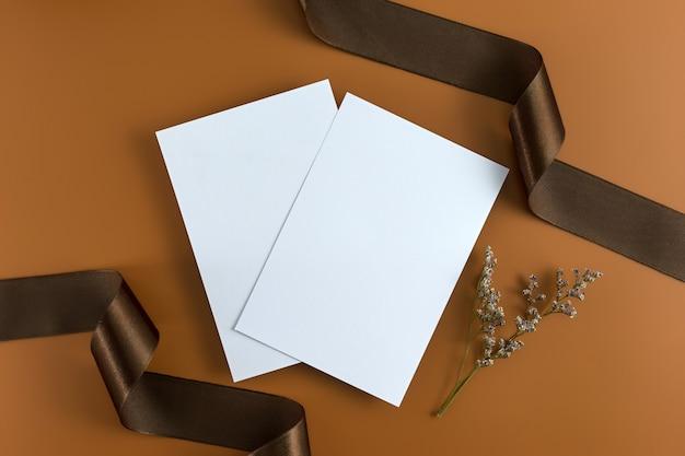 Koncepcja ślubu. zaproszenie na ślub na brązowym tle z wstążką.