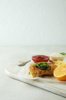 Koncepcja smaczne jedzenie ze smażoną rybą i frytkami na białym tle