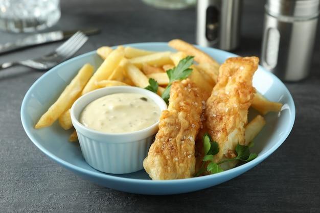 Koncepcja smaczne jedzenie ze smażoną rybą i frytkami na ciemnym stole z teksturą