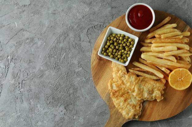 Koncepcja smaczne jedzenie ze smażoną rybą i frytkami na szaro teksturowanej