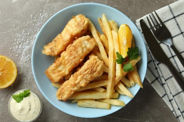 Koncepcja smaczne jedzenie ze smażoną rybą i frytkami na szarym stole z teksturą
