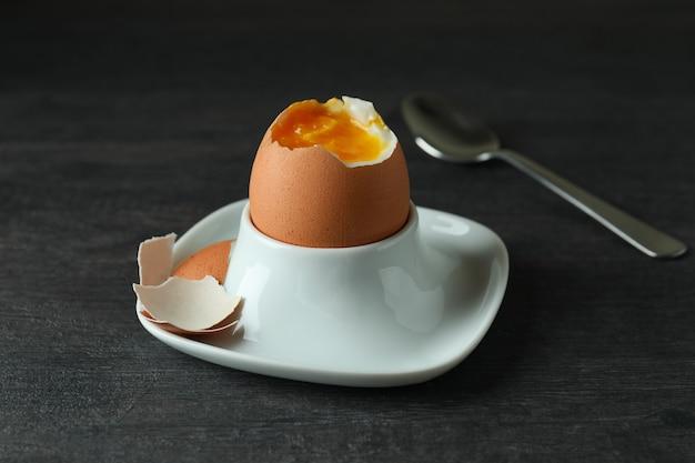 Koncepcja smaczne śniadanie z gotowanym jajkiem na ciemnym drewnianym stole