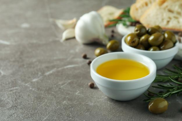 Koncepcja smacznego jedzenia z oliwą z oliwek na szarym stole z teksturą