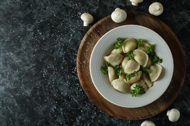 Koncepcja smacznego jedzenia z varenikami lub pierogami na ciemnym stole