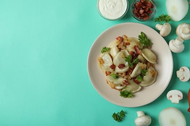 Koncepcja smacznego jedzenia z varenikami lub pierogami na miętowej powierzchni