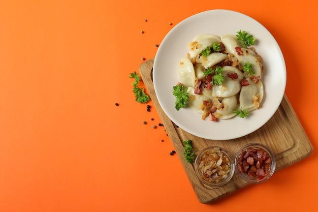 Koncepcja smacznego jedzenia z varenikami lub pierogami na pomarańczowej powierzchni