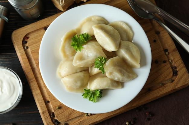 Koncepcja smacznego jedzenia z vareniki lub pierogami na drewnianym stole