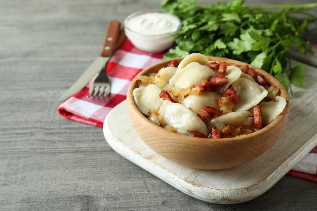 Koncepcja smacznego jedzenia z vareniki lub pierogami na szarym teksturowanym stole