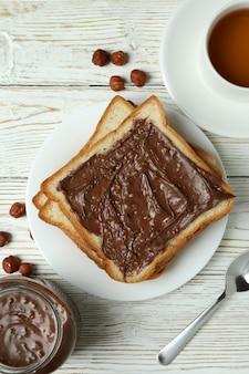 Koncepcja smacznego śniadania z pastą czekoladową na białym drewnianym stole