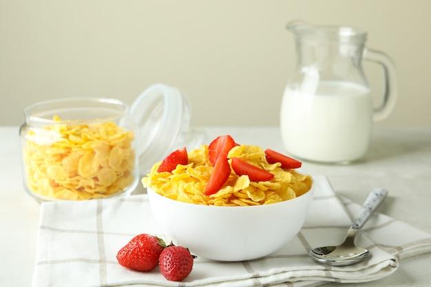 Koncepcja smacznego śniadania z płatkami kukurydzianymi na białym stole z teksturą