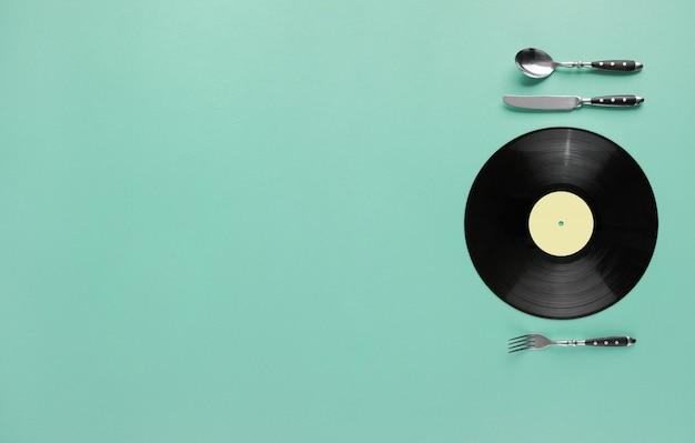 Koncepcja smaku muzyki z płyty winylowej jako talerz z nożem i widelcem na abstrakcyjnym tle pastelowych