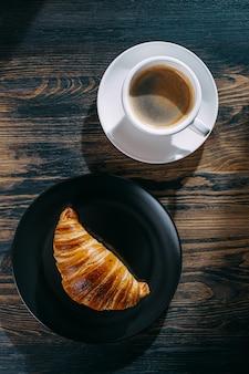 Koncepcja śniadania. gorący i świeży rogalik i filiżanka kawy