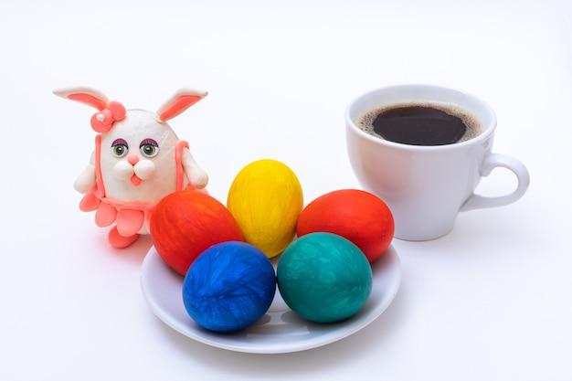Koncepcja śniadanie wielkanocne. ręcznie malowane pisanki, kubek kawy lub gorącej czekolady oraz domowy zajączek z plasteliny na białej powierzchni. koncepcja wesołych świąt.