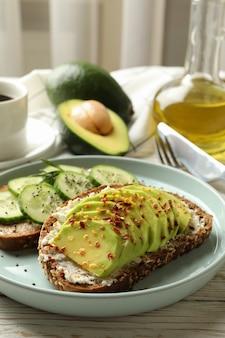 Koncepcja śniadanie z grzankami z awokado i ogórkiem na drewnianym stole