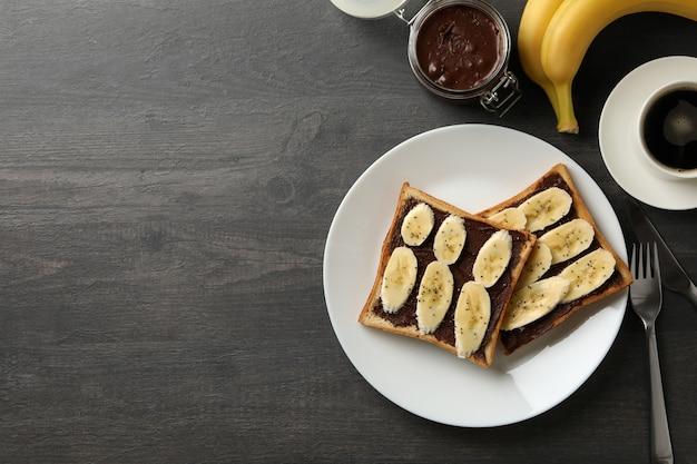 Koncepcja śniadanie z grzankami z bananem na podłoże drewniane