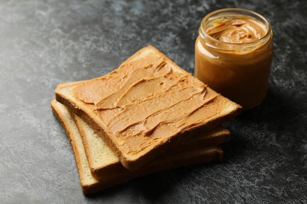 Koncepcja śniadanie z toastem masłem orzechowym na czarnym stole smokey