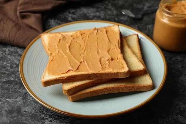 Koncepcja śniadanie z tosty z masłem orzechowym na czarnym stole smokey