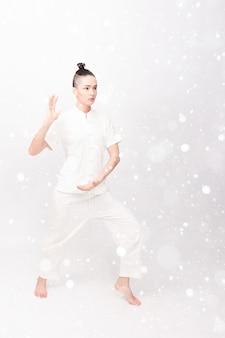 Koncepcja śniegu, zimy, bożego narodzenia, fitness, sportu, treningu i stylu życia - młoda kobieta robi ćwiczenia jogi. chińska umiejętność zarządzania energia qi na tle śniegu