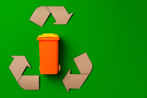 Koncepcja sortowania śmieci z kosza na śmieci zabawki na tle papieru widok z góry
